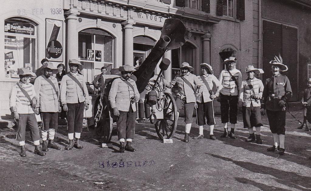 Narrengruppe mit Kanone vor dem Haus Vogt, Fasnacht 1938